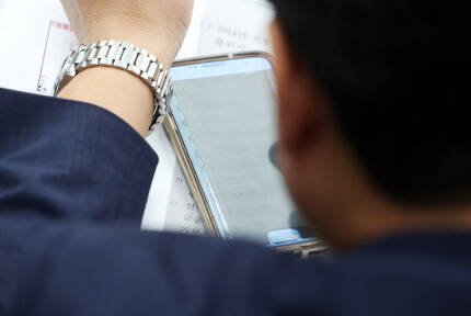 야당 소속 국회의원이 자신에게 쏟아진 비판 문자의 내용을 확인하고 있다. [출처=연합뉴스]