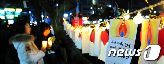 성탄절을 하루 앞둔 24일 제주시 제주시청 앞 도로에서 열린 제주시국촛불집회에서 참가자들이 소원트리에 소원을 걸고 있다.2016.12.24/뉴스1 © News1 이석형 기자