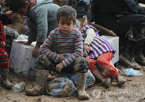 (모술<이라크> AFP=연합뉴스) 20일(현지시간) 이라크 모술 인근 하맘 알-알릴 캠프에서 어린이들이 앉아있는 모습.  현재 이라크군은 수니파 극단주의 무장단체 이슬람국가(IS)가 점령한 모술 서부 지역에 대한 탈환작전을 진행 중이나, 올드시티 등 일부 지구에선 IS 잔존 세력의 거센 저항에 직면해 있다.