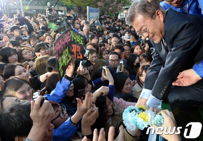 문재인 더불어민주당 대선후보가 21일 오후 인천시 부평역 앞 광장에서 진행된 인천지역 집중유세에서 시민들의 손을 잡고 있다. 2017.4.21/뉴스1 © News1 허경 기자