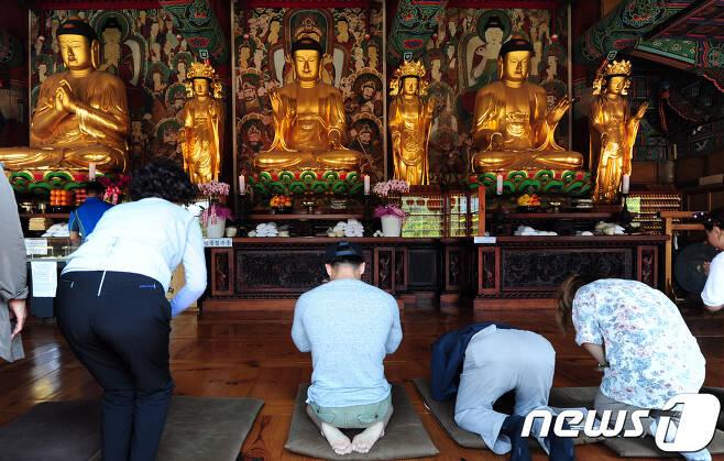 불교 신자들이 불상에 기도를 드리고 있다./뉴스1DB