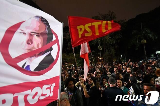 브라질 시민들이 18일(현지시간) 미셰우 테메르 대통령에 반대하는 시위를 벌이고 있다. © AFP=뉴스1