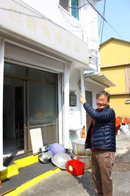 서영남 민들레국수집 대표가 지난 26일 15년 전 내걸었던 빛 바랜 식당 간판을 가리키면서 지나온 세월을 회고하고 있다.