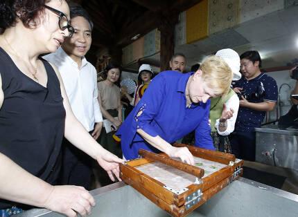 7일 전주 한옥마을 한지원에서 해리스 주한 미국대사의 부인 브루스 브래들리(파란색 남방) 여사가 전통 방식으로 한지를 만들고 있다. [사진 전주시]