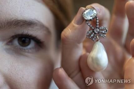 경매업체 소더비 직원이 마리 앙투아네트가 소유했던 다이아몬드 진주 목걸이 펜던트를 들어 보이고 있다. 이 보석들은 14일(현지시간) 경매에 출품된다. [EPA=연합뉴스]