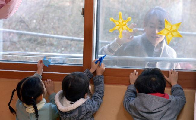한 학부모가 어린이집에서 놀고있는 아이를 창 박에서 지켜보고 있다.