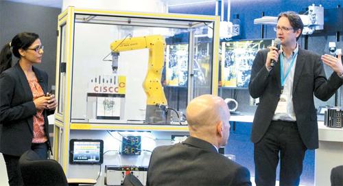 일본 로봇 제조기업인 화낙은 미국 통신업체 시스코와 제휴해 사물인터넷(IoT) 기술을 이용하여 로봇의 고장을 사전에 예측함으로써 공장을 멈추지 않고 가동할 수 있는 시스템을 구축했다. 지난해 10월 미국 샌프란시스코 시스코 본사에서 직원들이 기자들 앞에서 화낙의 IoT 로봇을 시연하고 있다. [매경DB]