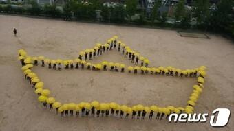 인천 석남중학교 학생들이 13일 학교 운동장에서 세월호 기억 노란우산 프로젝트 플래시몹을 하는 모습. 2016.7.13 © News1 주영민 기자