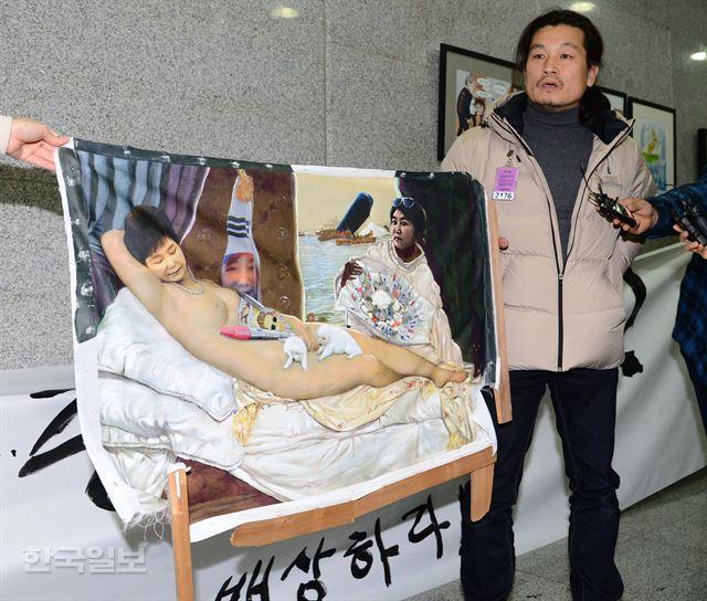 보수단체 회원들이 부순 '더러운 잠'의 이구영 작가가 지난 24일 서울 여의도 국회의원회관 로비에서 파손된 자신의 작품을 들고 기자회견을 하고 있다. 오대근 기자 inliner@hankookilbo.com