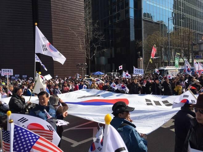 25일 오후, 서울 중구 대한문 인근에서 대통령 탄핵기각을 위한 국민 총궐기운동본부가 주최한 '제14차 탄핵기각 총궐기 국민대회'가 열렸다. 참가자들은 대형 태극기를 들고 탄핵 반대 집회에 참여했다.