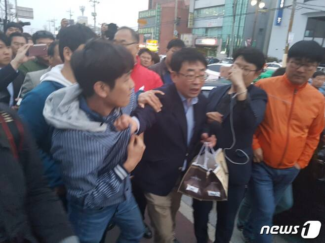 21일 오후 경주역에서 열린 홍준표 자유한국당 대통령 후보 유세현장에서 홍 후보 사퇴를 촉구한 한 피켓시위 참가자와 지지자들이 실랑이를 벌이고 있다. © News1