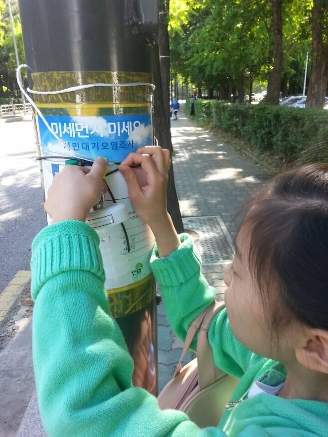 지난달 14~15일 진행된 '미세먼지! 미세요!' 프로젝트에 참가한 시민이 가로등에 총부유먼지와 이산화질소를 측정할 수 있는 측정 키트를 설치하고 있다. 녹색연합 제공