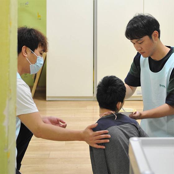 경기도 광주시에 있는 중증장애요양시설 '초록우산어린이재단 한사랑마을'에서 김준영 기자(오른쪽)가 한 장애인의 식사를 돕고 있다. 이곳에선 28명의 사회복지사가 일한다. [사진 초록우산어린이재단]