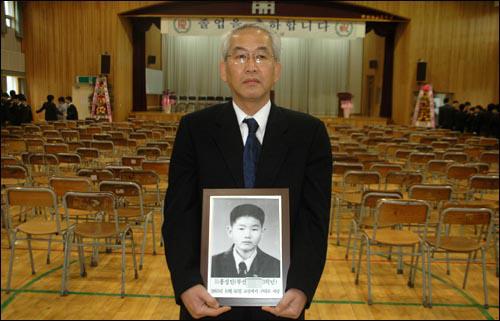 홍권식씨는 2007년 2월 아들 성인군의 영정 사진을 들고 개성중 졸업식에 갔다. [사진 오마이뉴스]