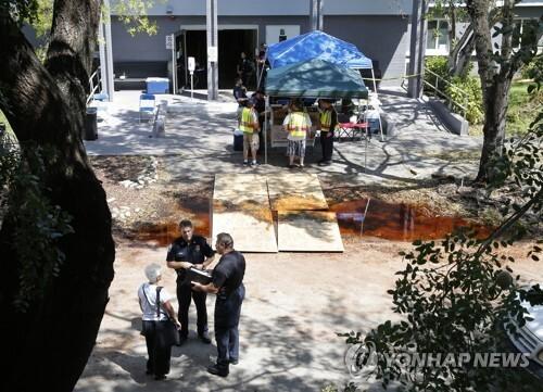 사고가 난 요양원 앞에서 경찰들이 직원들을 조사하고 있다. [AP=연합뉴스]