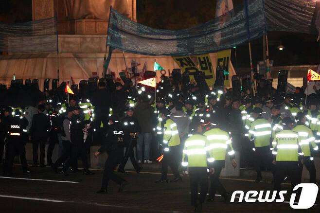 7일 오후 서울 광화문광장에서 열린 'NO WAR 평화염원 촛불문화제'에서 참가자들이 도널드 트럼프 미국 대통령의 차량이 지나가는 방향을 향해 물건을 던지자 경찰이 가림막으로 이를 막고 있다. 2017.11.7/뉴스1 © News1 신웅수 기자