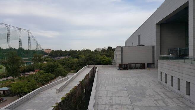 문화체육관광부가 국립문학관 신축 터로 지목한 서울 용산 국립중앙박물관 옆 공지. 박물관 건물과 왼쪽의 미8군 골프연습장 그물망 사이 숲 공간이 예정 터다.