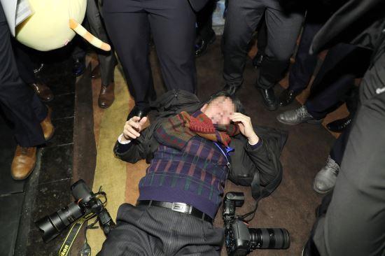 14일 오전 베이징 국가회의 중심 B홀에서 열린 문재인 대통령 '한·중 경제·무역 파트너십 개막식'에서 한국의 사진기자가  중국측 경호원에게 일방적으로 폭행 당해 쓰러져 있다. 베이징=청와대사진기자단