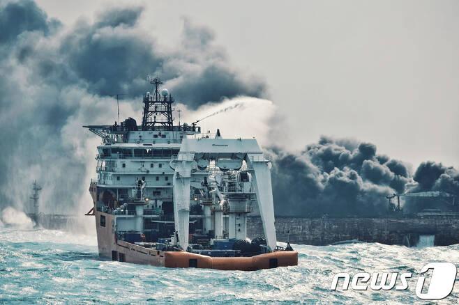 10일 (현지시간) 한국으로 향하다 중국 동중국해에서 침몰한 이란 유조선 '산치호'의 불을 끄기위해 중국 보급선이 물을 뿌리고 있다. © AFP=뉴스1