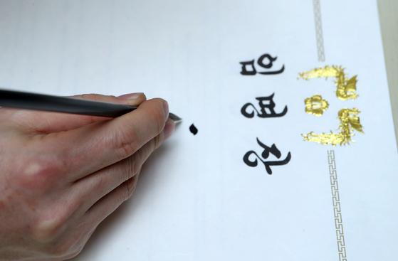 김이중 사무관이 붓에 벼루에 있는 먹물을 적신 뒤 임명장을 작성하고 있다. [최정동 기자]