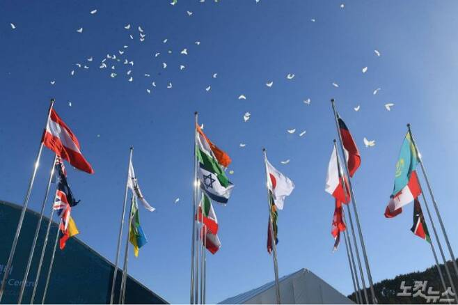 1일 오후 강원도 평창동계올림픽 선수촌에서 열린 개촌식에서 만국기 뒤로 평화의 비둘기 풍선이 날아가고 있다. (사진=이한형 기자)