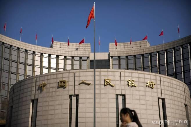 【베이징=AP/뉴시스】중국 중앙은행인 인민은행이 현금 수요가 급증하는 춘절(구정· 2월16일)를 앞두고 상업은행의 지급준비율(지준율)을 낮추는 조치를 취하기로 했다. 지난 3월10일 베이징 인민은행 본사 앞으로 행인들이 지나가고 있다. 2017.12.29      <저작권자ⓒ 공감언론 뉴시스통신사. 무단전재-재배포 금지.>
