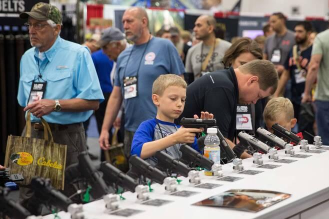 미국총기협회(NRA) 주최로 총기전시회가 텍사스주 댈러스 카이 베일리 허치슨 컨벤션센터에서 6일까지 열리고 있다. 한 어린이가 권총을 살펴보고 있다. [AFP=연합뉴스]