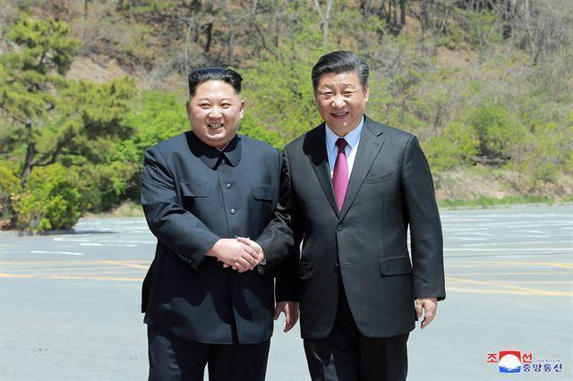 김정은 북한 국무위원장과 시진핑 중국 국가주석이 지난달 8일 다롄 동쪽 외곽 해변에 있는 방추이다오 영빈관에서 만나 악수하며 기념촬영을 하고 있다. 조선중앙통신 연합뉴스