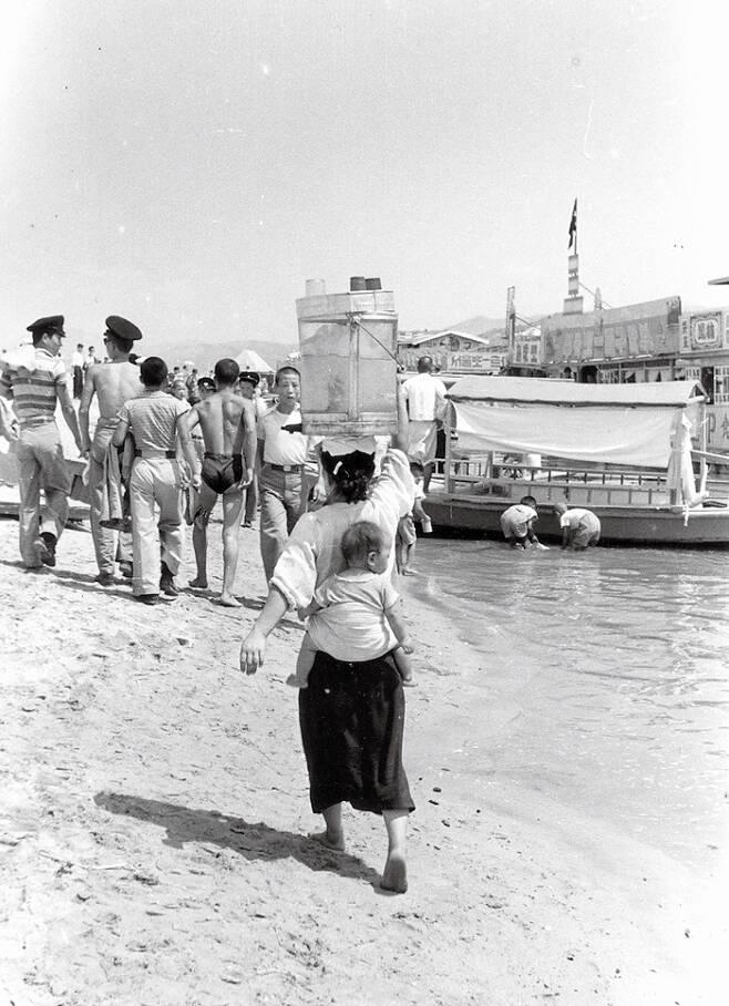 1957년 여름, 1대 임인식 작가가 촬영한 한강 백사장. 더위 속에서 냉차를 파는 여인이 아이를 등에 업고 손님들을 찾아 걸어가고 있다.