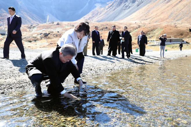 문재인 대통령이 20일 오전 김정은 국무위원장과 백두산 천지를 산책하던 중 천지 물을 물병에 담고 있다. 평양사진공동취재단