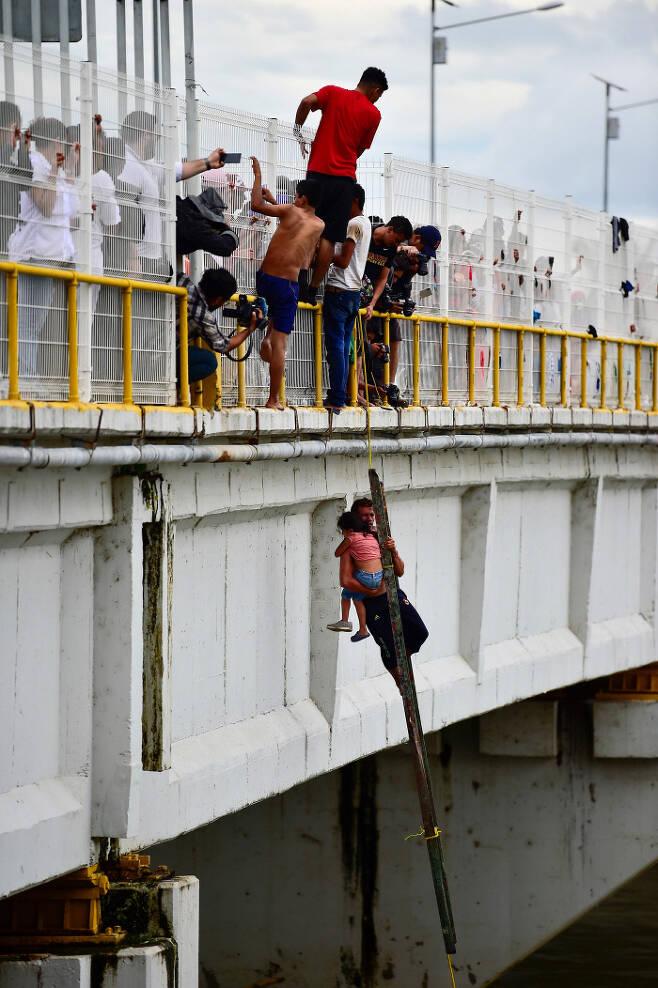 과테말라·멕시코 국경도시 시우다드 이달고에서 20일(현지시간) 온두라스 이민자들이 아이를 안고 강을 건너려는 다른 이민자를 도와주고 있다. AFP=연합뉴스
