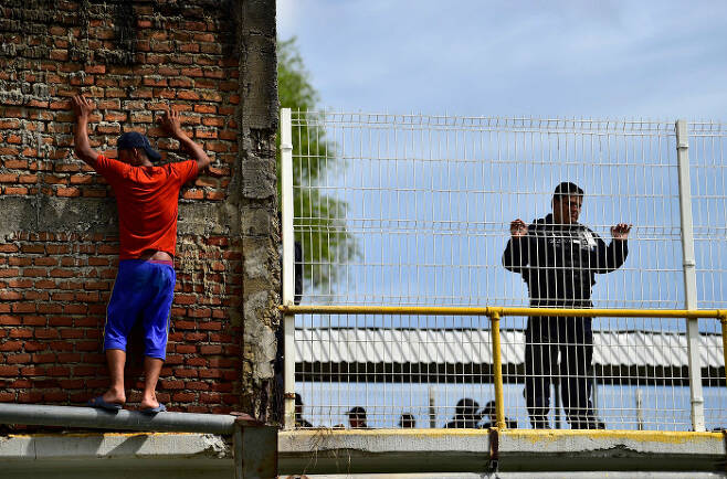 과테말라와 멕시코 국경 수치아떼 강 다리 위에서 멕시코 경찰의 눈을 피해 강으로 뛰어들 준비를 하고 있는 온두라스 이민자. AFP=연합뉴스