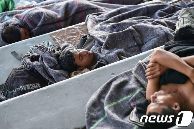 미국 남부 국경을 향해 북상하고 있는 중미 출신 이민자들이 5일(현지시간) 멕시코 수도 멕시코시티 소재 헤수스 마르티네스 스타디움에 설치된 임시수용시설에서 휴식을 하고 있다. © AFP=뉴스1