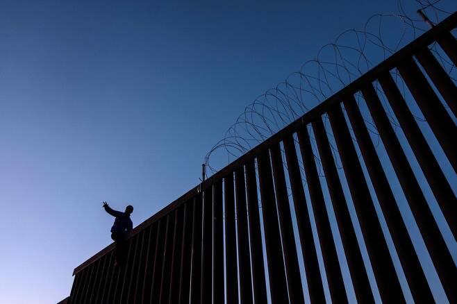 한 이민자가 18일(현지시간) 멕시코 티후아나 미국-멕시코 국경 담장 위에 서 있다. [AFP=연합뉴스]