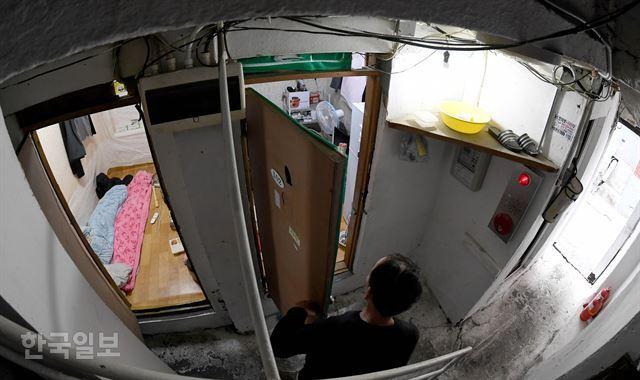 서울 용산구 일대의 한 쪽방 내부를 주민이 들여다보고 있다. 서재훈 기자