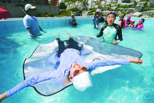 충북 제천 홍광초등학교에서 지난달 5일 열린 '이동식 생존수영 교실'에서 학생들이 돗자리를 이용해 물에 뜨는 체험을 하고 있다.