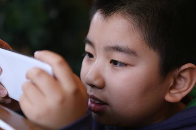 ▲스마트폰을 보고 있는 어린이. ⓒ게티이미지.