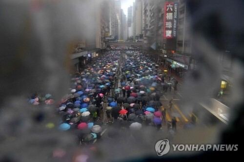 홍콩의 빗속 시위 (홍콩 AP=연합뉴스) 홍콩 정부의 '복면금지법' 시행에 반대하는 시위자들이 6일 비가 내리는 가운데 홍콩 쇼핑가 코즈웨이베이에서 우산을 쓴 채 행진하고 있다. bulls@yna.co.kr