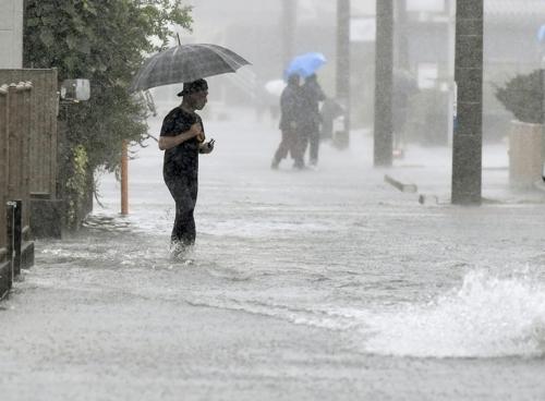 태풍 하기비스 영향으로 물에 잠긴 日 도로 (시즈오카 교도=연합뉴스) 12일 제19호 태풍 하기비스의 영향으로 폭우가 쏟아진 일본 시즈오카(靜岡)시의 도로가 물에 잠긴 가운데 행인이 걸어가고 있다. 2019.10.12