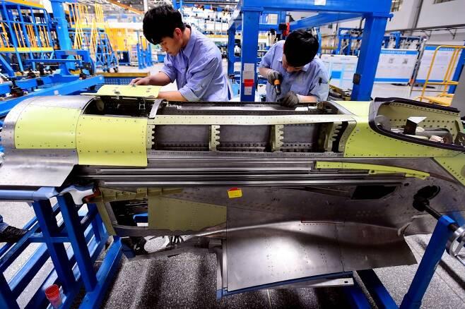 중국 랴오닝성 선양에 위치한 중국 국영 항공기 제작사 코맥(COMAC) 공장에서 직원들이 자체 개발 항공기 'C919'의 엔진 부품을 살펴보고 있다. /사진=AFP