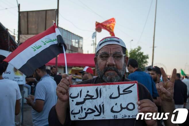"""1일(현지시간) 이라크 반정부에 시위에 참석한 한 남성이 """"모든 피해는 정당들의 몫""""이라고 적힌 플래카드를 들고 있다. © AFP=뉴스1"""
