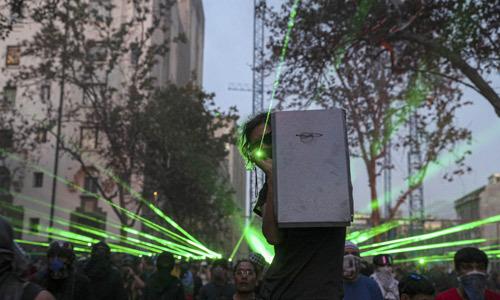 칠레의 반정부 시위대가 14일(현지시간) 수도 산티아고에서 경찰을 향해 레이저 포인터를 비추고 있다. 연합뉴스