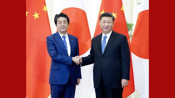 시진핑 중국 국가주석과 아베 신조 일본 총리가 지난 24일 악수를 나누고 있다. [중국 신화망 캡처]