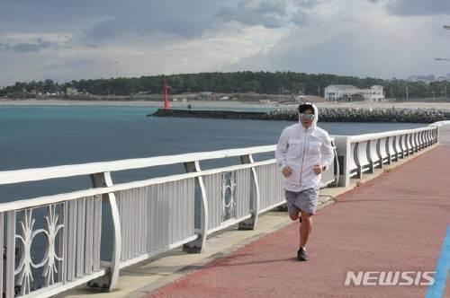 포근한 날씨를 보인 7일 오전 제주시 이호테우해변 해안도로에서 한 시민이 반바지 차림으로 달리기 운동을 하고 있다. 뉴시스