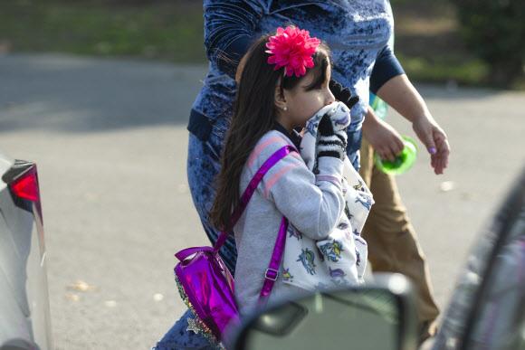 14일(현지시간) 항공유가 비처럼 내린 미국 로스앤젤레스 파크애비뉴 초등학교에서 한 학생이 수건으로 코를 막고 이동하고 있다. AP