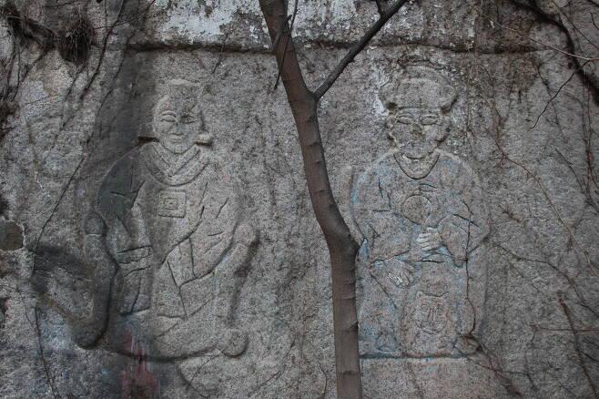 새로 발견된 부부 산신 암각. 오른쪽 남자 산신 아래에 호랑이 얼굴이 보인다.
