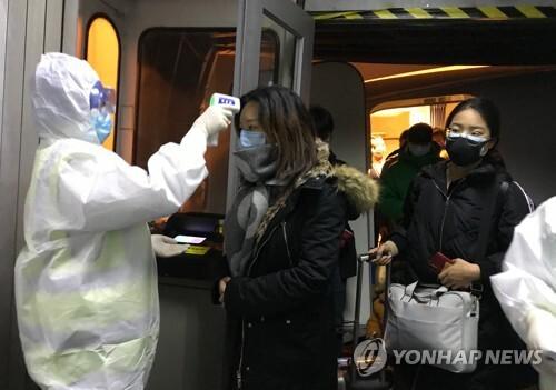 지난 22일(현지시간) 중국 우한에서 온 승객들을 대상으로 한 베이징 공항 당국의 체온 검사 [AP=연합뉴스]