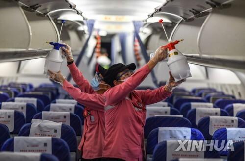 중국 하이난성 하이커우에 도착한 한 항공기에서 방역 작업 중인 직원들 [신화=연합뉴스]