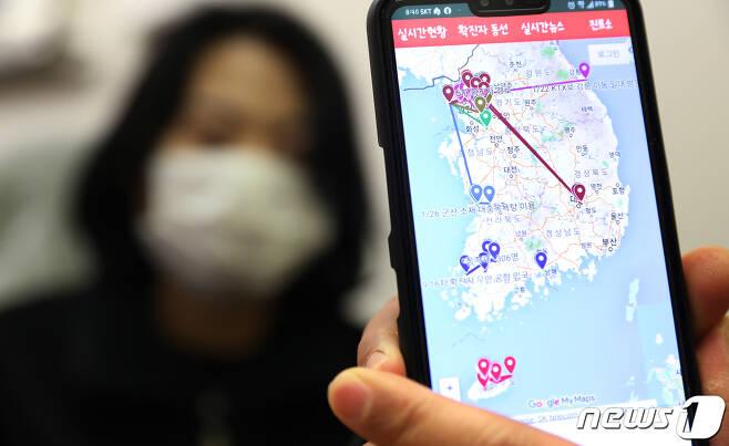 서울 도심에서 한 시민이 스마트폰 애플리케이션을 이용해 실시간 국내 감염자 확진자 동선을 살펴보고 있다. 2020.2.6/뉴스1 © News1 송원영 기자