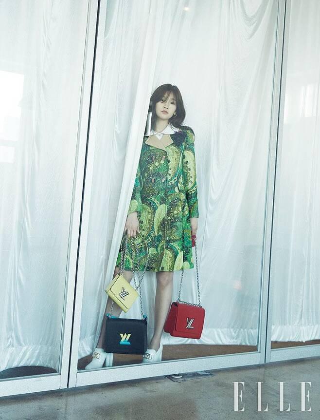 현란한 프린트의 미니 트렌치코트와 윙 칼라 화이트 셔츠, V 모티프 이어링, 옐로·레드·블랙 컬러의 트위스트 백, 화이트 부티는 모두 Louis Vuitton.